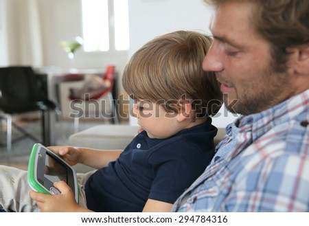 Daddy with son playing with video game player - stock photo