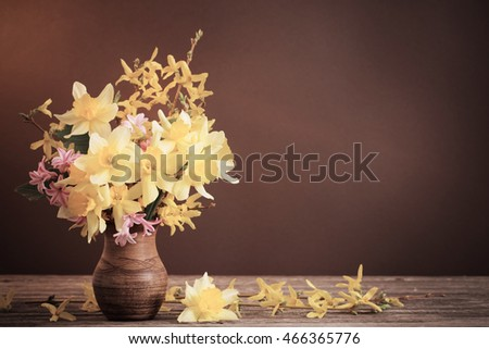 Daffodil in vase on brown background