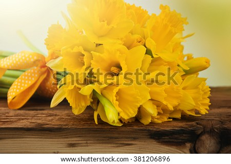 Daffodils on wooden background. - stock photo