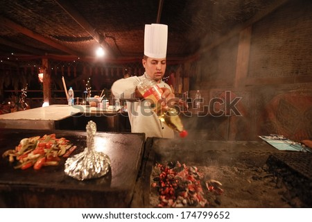 DAHAB, EGYPT - JANUARY 28, 2011: Egyptian cook prepares traditional meal. Egyptian food is a mixture of all the different civilisations that came to Egypt in the history of its existence. - stock photo