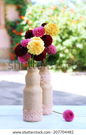 Dahlia flowers in vase on table, outdoors - stock photo