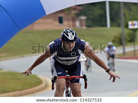 DAHLONEGA, GA/USA - SEPTEMBER 30: Unidentified man coming across the finish line at the Three and Six Gap Century ride, September 30, 2012 in Dahlonega GA. - stock photo