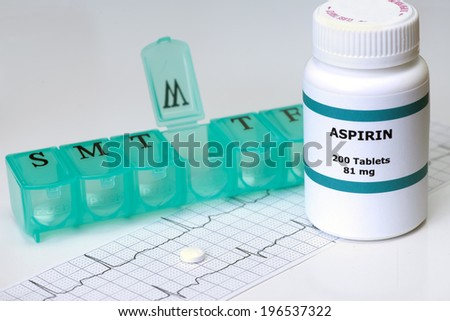 Daily aspirin with electrocardiograph and medication dispenser. - stock photo