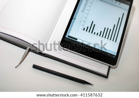 Daily log with a pencil and laptop lying on the plane at an angle - stock photo