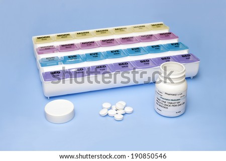 Daily medication dispenser with pills and prescription bottle. - stock photo