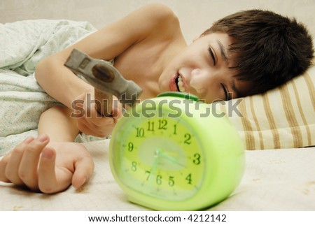 Daily morning battle between boy and alarm clock - stock photo