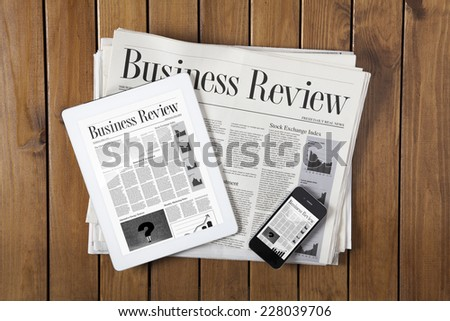 Daily newspaper stack and tablet pc on the wooden table - stock photo