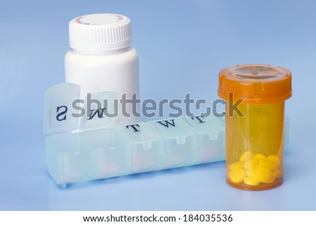 Daily pill dispenser and medication bottles on blue background. - stock photo