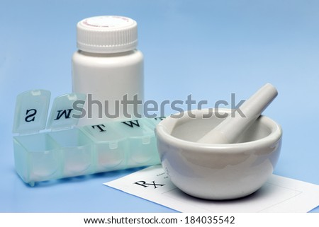 Daily pill dispenser, mortar and pestle, and medication bottles on blue background. - stock photo