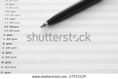Daily planner with a pen. Focus at the tip. - stock photo