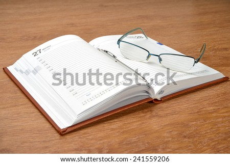 Daily planner with glasses and pen on the table