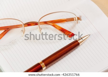 Daily planner with glasses and pen on the table. Selective focus - stock photo