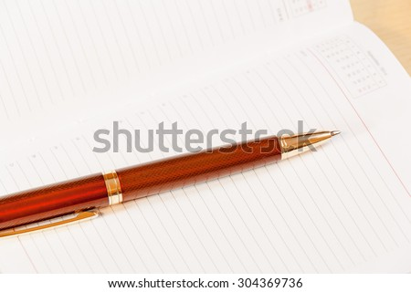 Daily planner with  pen on the table - stock photo