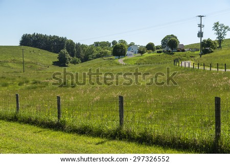Dairy farm in rolling hills of Appalachian Mountains in Virginia with cattle grazing in background. - stock photo