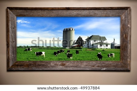 Dairy farm scene image in rustic wooden frame. Weathered barn wood frame hangs on wall. - stock photo