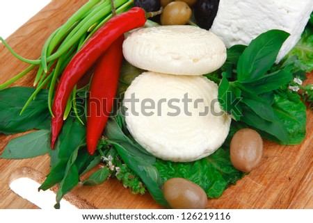 dairy food : feta white cheese cubes and round served on wooden cut plate with green leaves and olive oil isolated over white background - stock photo