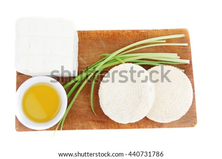 dairy food : feta white cheese cubes with olive oil on small saucer on cut wooden plate isolated over white background - stock photo