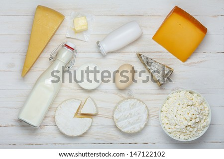 Dairy products assortment on wooden table - milk, cheese, egg, yogurt, sour cream, cottage cheese and butter - stock photo