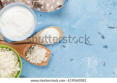 Dairy products on stone table. Sour cream, cheese curd. Top view with copy space