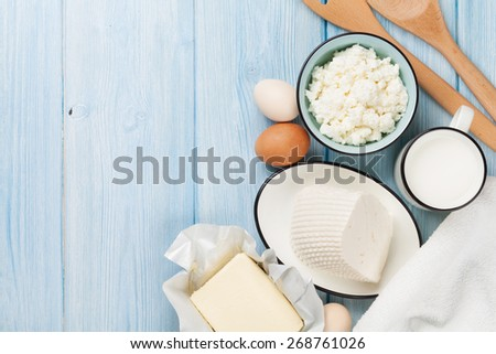 Dairy products on wooden table. Milk, cheese, egg, curd cheese and butter. Top view with copy space - stock photo