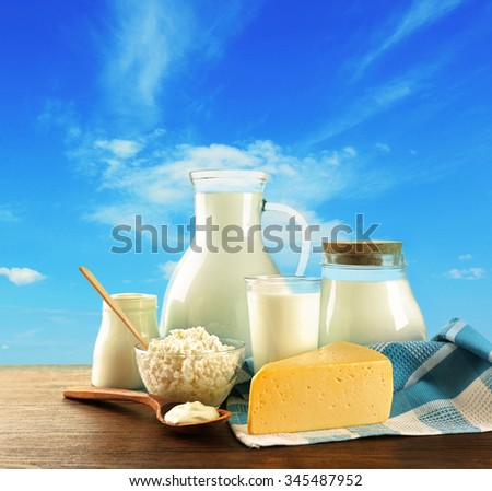 Dairy products on wooden table on sky background - stock photo
