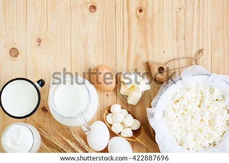 Dairy products on wooden table. Sour cream, milk, cottage cheese, mozzarella, eggs and butter. Top view with copy space