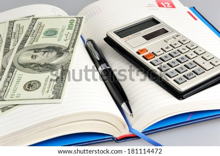 Dairy with black pen, calculator and money close-up - stock photo