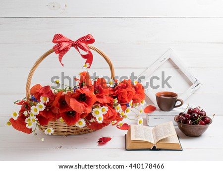 Daisy and poppies bouquet in basket with open book and cup tea, sweet cherry, photo frame on background of white wooden planks in provence style. Home interior. - stock photo