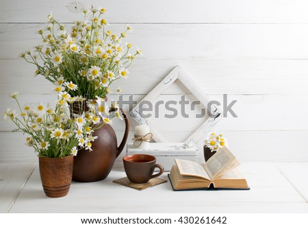 Daisy bouquet in clay jug with open book and cup tea; photo frame; candle on background of white wooden planks in scandinavian style. Home interior. - stock photo