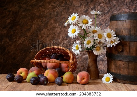 Daisy flowers in a vase with fresh fruits in a vicker basket on a wodden table - stock photo