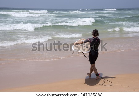 DAKAR, SENEGAL - JUNE 01, 2014: A young tourist heads towards the sea with her surfboard at Yoff Beach