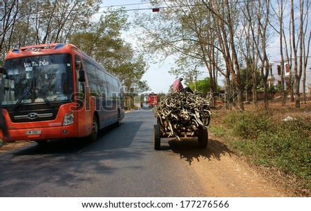 DAKLAK, VIETNAM- FEB 8 Traffic of transport vehicle on highway, the asphalt road pass jungle, passenger car and farm vehicle moving on day, Viet Nam, Feb 8, 2014
