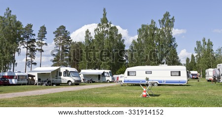DALARNA, SWEDEN ON JULY 04. View of a camping with caravans and campers on July 04, 2015 in Dlarana, Sweden. Sunshine, green lawn and blue sky. Typical by lake Siljan.