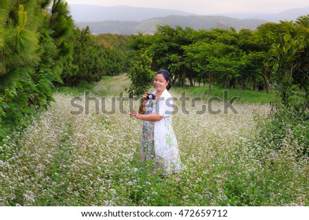 Dalat city, Vietnam - August 14, 2016 : a woman is very happy with her camera on buckwheat flower field