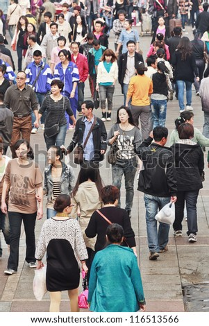 DALIAN-CHINA-OCT. 14, 2012. Crowd on Oct 14, 2012 in Dalian. China's estimated population is 1,338,612,968. 21% of population (145,461,833 males; 128,445,739 females) are 14 years old or younger. - stock photo