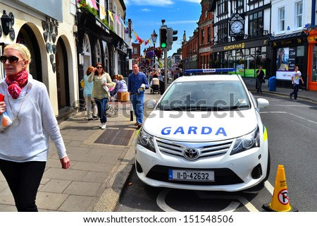 DALKEY, IRELAND - JUNE 18: Unidentified people walk past a police car during the visit of U.S. First Lady, Michelle Obama, on June 18, 2013 in Dalkey, Ireland   - stock photo