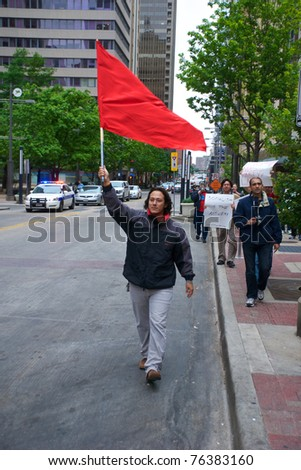DALLAS - MAY 1: An unidentified demonstrator carries a red flag down Main Street on May 1, 2011 in Dallas, Texas. A red flag flown on May Day is generally considered an endorsement of socialism. - stock photo