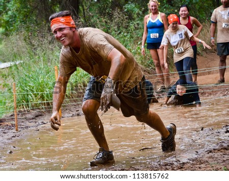 DALLAS, TEXAS - SEPTEMBER 15: Unidentified male participant passes through a mud pit in the Dash of the Titans Mud Run Race on September 15, 2012 in Dallas, Texas. - stock photo