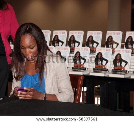 DALLAS, TEXAS/USA-JULY 11: Venus Williams signing copies of her newly released book on July 11,2010 in Dallas. Williams texting before beginning book signing. - stock photo
