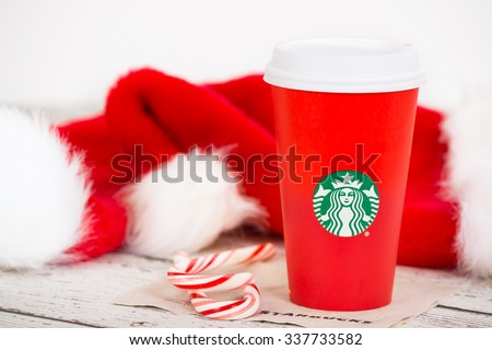 DALLAS, TX - NOVEMBER 10, 2015: A cup of Starbucks popular holiday beverage, served in the new 2015 designed red holiday cup. Displayed with Christmas hats and candy canes on white rustic table.  - stock photo