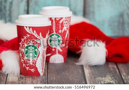 DALLAS, TX - NOVEMBER 15, 2016: Starbucks popular holiday beverages, served in the new 2016 designed red holiday cups. Displayed with Christmas hats on wooden rustic table.