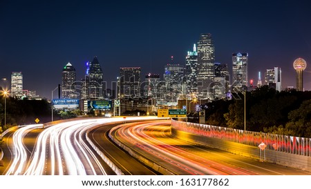 DALLAS, USA - OCTOBER 25: Dallas skyline by night on October 25, 2013 in Dallas, USA. The rush hour traffic leaves light trails on I-30 (Tom Landry) freeway.