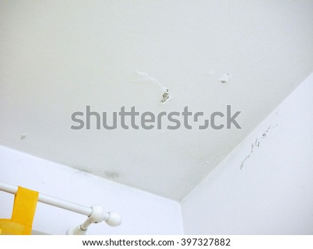 Damage caused by damp and moisture on a wall and ceiling due to water infiltration from apartment above - stock photo