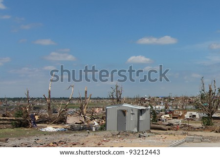 Damage from a tornado can forever change the landscape, leaving behind near total destruction of shrubs and trees, as well as man made structures. - stock photo