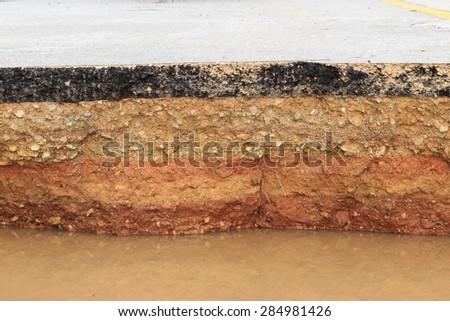 Damaged asphalt. Layer of clay that were eroded under the asphalt - stock photo