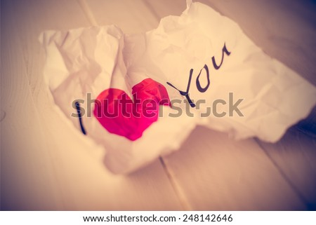 "Damaged card paper with the inscription ""I love You"" - a symbol of rejected love. Vintage retouching."