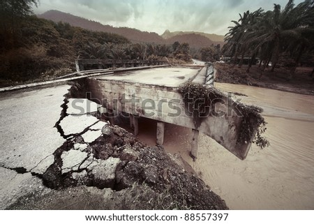 Damaged concrete bridge over tropical river in mountain. Consequences of flood. - stock photo