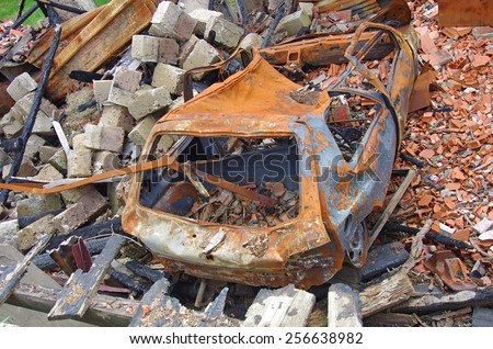 Damaged house after arson fire. remnants of burned car, insurance theme. - stock photo
