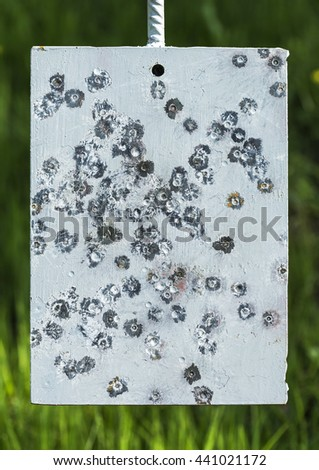 Damaged metal target with bullet marks. - stock photo