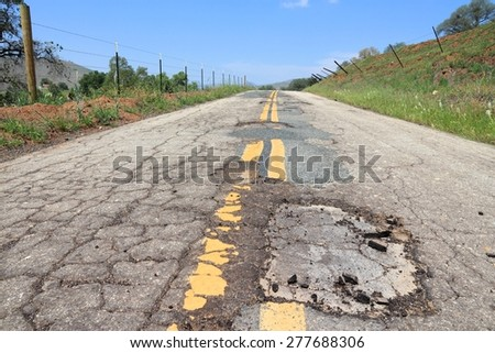Damaged road of Yokohl Drive in California, USA - cracked asphalt blacktop with potholes and patches.